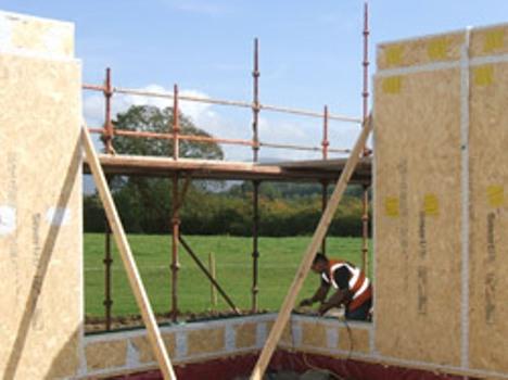 Специалист, использующий целлюлозные панели в строительстве